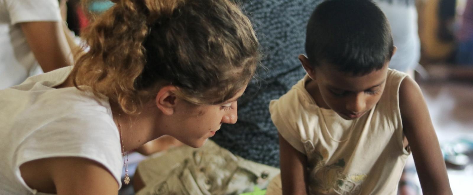 Una voluntaria ayuda a un niño con ejercicios básicos de inglés durante su programa de voluntariado en verano para jóvenes en Sri Lanka.